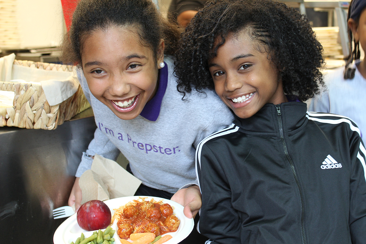 Two black school aged girls enjoying school lunch.