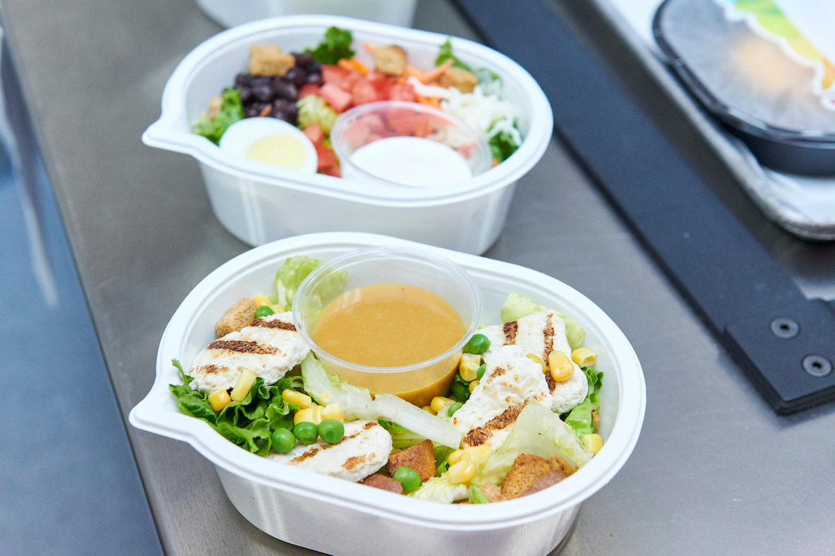 A healthy school lunch salad with grilled chicken and dressing